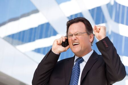 Excited Businessman Using Cell Phone Clinches His Fist in Joy Outside of Corporate Building. Stock Photo - 6633587