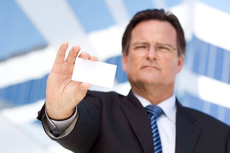 Handsome Businessman in Suit and Tie Holds Out Blank Business Card in Front of Corporate Building. photo
