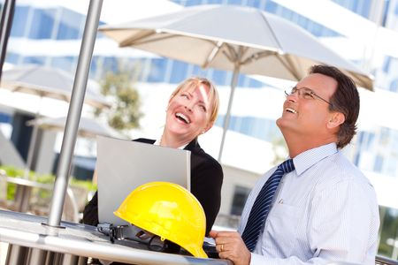 Handsome Businessman and Attractive Businesswoman Laughing While Working on the Laptop Outdoors. photo