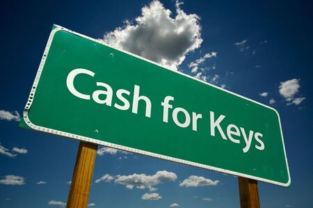Cash for Keys Green Road Sign on Dramatic Blue Sky with Clouds. photo
