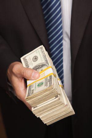 cash in hand: Empresario cuidado sobre la pila de proyectos de ley de cien d�lares.