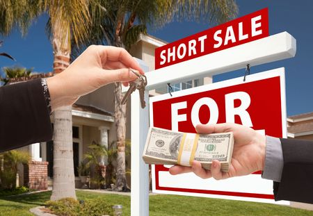 sales lady: Handing Over Cash For House Keys and Short Sale Real Estate Sign in Front of Home.