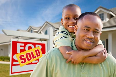 Happy African American Father and Son in Front of New Home and Sold Real Estate Sign. Stock Photo - 6689559
