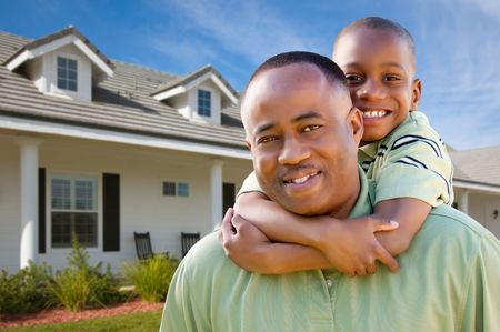 Happy African American Father and Son Outside of their Home.