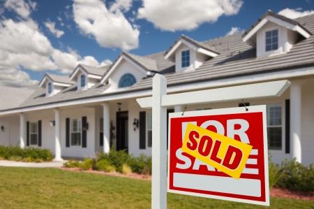 nieruchomosci: Sprzedany Strona główna na znak sprzedaży nieruchomoÅ›ci z przodu nowy dom - prawo w obliczu. Zdjęcie Seryjne