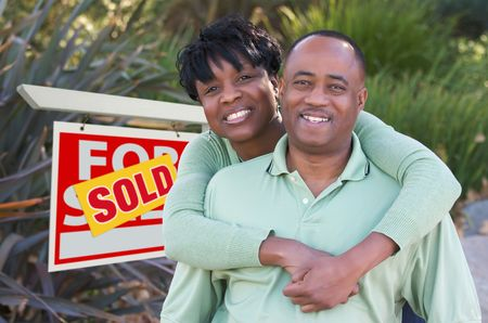 Happy African American Couple in Front of Sold Home For Sale Real Estate Sign. Stock Photo