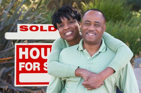 Happy African American Couple in Front of Sold Home For Sale Real Estate Sign. Imagens