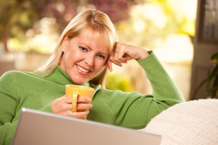 warm drink: Beautiful, Smiling Woman Enjoys Her Warm Drink and Laptop Relaxing Day.