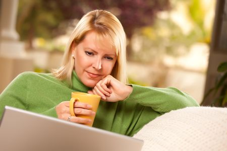 Beautiful, Smiling Woman Enjoys Her Warm Drink and Laptop Relaxing Day. photo