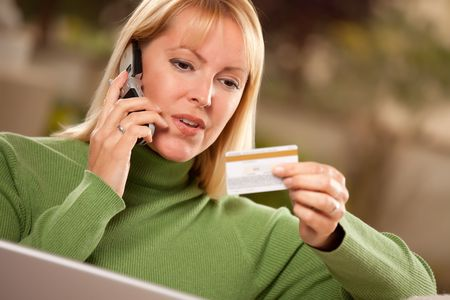 Cheerful Woman on Her Phone and Laptop with Credit Card. photo
