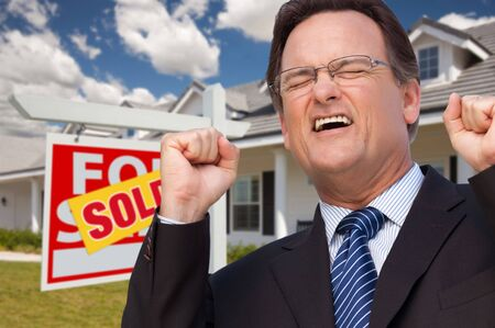 real: Excited Man in Front of Sold Real Estate Sign and Beautiful New House. Stock Photo