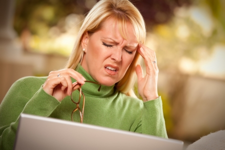 grimacing: Grimacing Woman with Glasses Using Laptop Suffering a Painful Headache.
