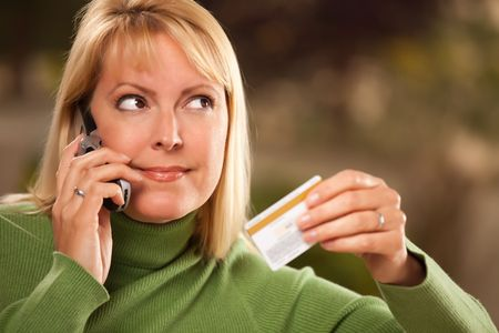 Cheerful Smiling Woman Using Her Phone with Credit Card in Hand. photo