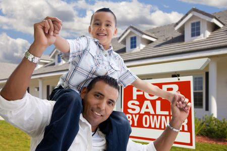 Excited Hispanic Father and Son with For Sale By Owner Sign in Front of House. photo