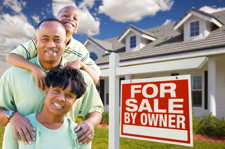 Attractive, Happy African American Family with For Sale By Owner Sign in Front of House. photo