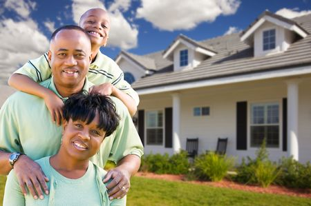 front of: Attractive African American Family in Front of Beautiful House. Stock Photo