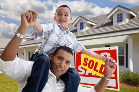 Excited Hispanic Father and Son with Sold For Sale Real Estate Sign in Front of House. photo
