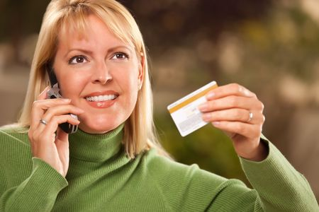 charge card: Cheerful Smiling Woman Using Her Phone with Credit Card in Hand. Stock Photo
