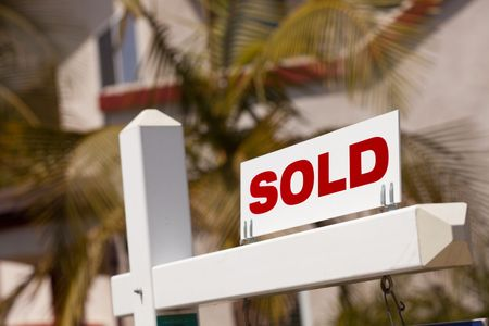 Close-up of Sold Real Estate Sign in Front of House. photo