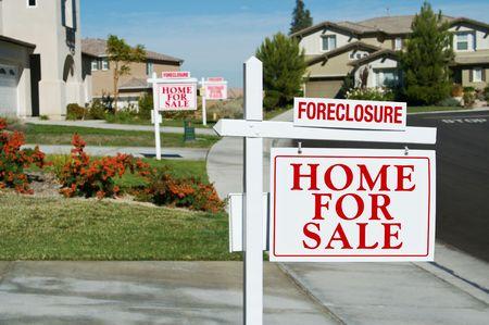 家の前に販売の不動産のサインのための抵当流れの家の行。 写真素材