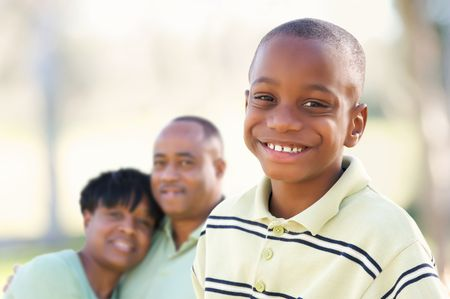 Handsome African American Boy with Proud Parents Standing By in the Park. photo