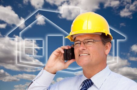 Contractor in Hardhat on His Cell Phone Over House Icon and Blurry Clouds. photo