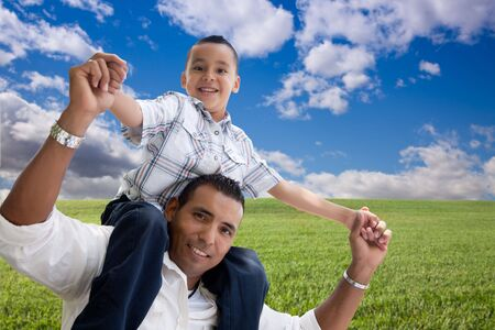 Happy Hispanic Father and Son Over Grass Field, Clouds and Blue Sky. photo