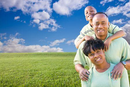 Feliz familia afroamericana en el campo de césped, las nubes y Blue Sky - sala para su propio texto a la izquierda.
