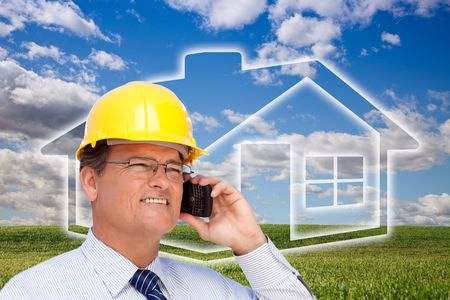 Contractor in Hardhat on His Cell Phone Over House Icon, Empty Grass Field and Deep Blue Sky with Clouds. photo