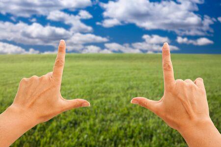 Mains féminines faisant un cadre sur l'herbe et le ciel.