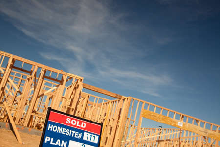Sold Lot Real Estate Sign at New Home Framing Construction Site Against Deep Blue Sky. Stock Photo