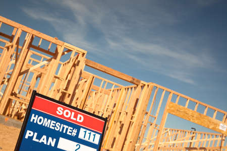 Sold Lot Real Estate Sign at New Home Framing Construction Site Against Deep Blue Sky. Stock Photo - 6971213