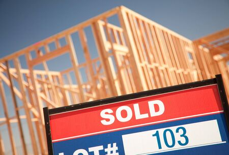 housing lot: Sold Lot Real Estate Sign at New Home Framing Construction Site Against Deep Blue Sky. Stock Photo