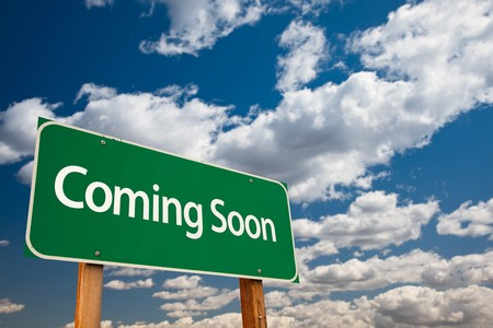 soon: Coming Soon Green Road Sign with Copy Room Over The Dramatic Clouds and Sky. Stock Photo