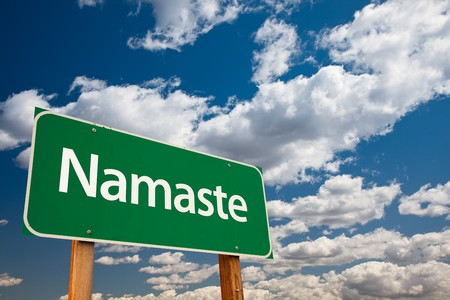 namaste: Namaste Green Road Sign with Copy Room Over The Dramatic Clouds and Sky. Stock Photo
