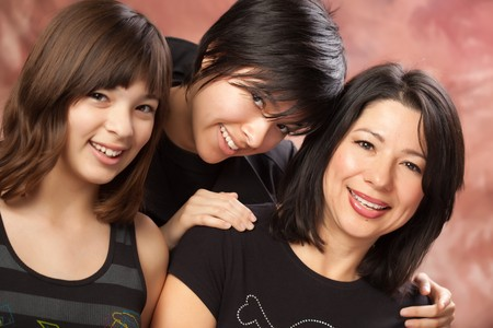 Attractive Multiethnic Mother and Daughters Studio Portrait. photo