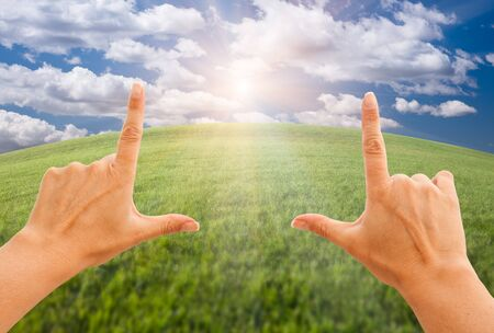 clouds making: Female Hands Making a Frame Over Arched Horizon of Grass Field, Sunlight, Clouds and Sky.