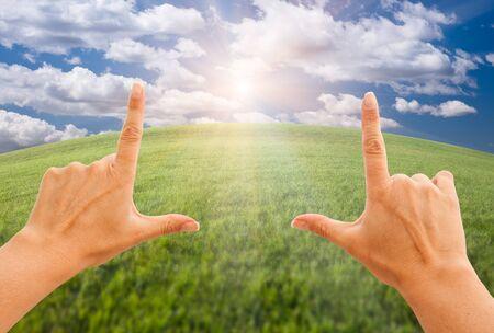 arcuate: Mani femminile effettuare un frame su Horizon arcuato di Grass Field, luce del sole, nuvole e cielo. Archivio Fotografico