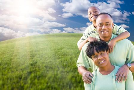mujeres africanas: Feliz familia afroamericana sobre nubes, Sky y Horizon arqueado del campo de c�sped.  Foto de archivo
