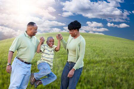 madre tierra: Feliz familia afroamericana Roll Over nubes, Sky y Horizon arqueado del campo de c�sped.