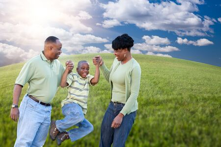 earth friendly: Happy African American Family Playing Over Clouds, Sky and Arched Horizon of Grass Field.
