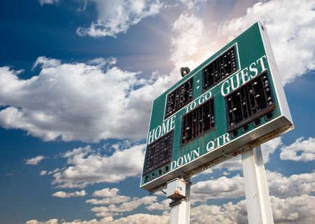 scoreboard: HIgh School Score Board on a Dramatic Blue Sky with Clouds and Sun Rays. Stock Photo