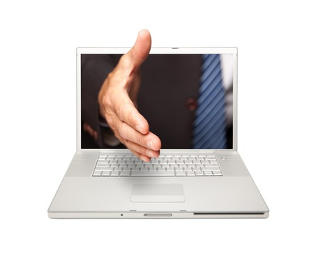 technology deal: Man Reaaching for a Handshake Through Laptop Screen Isolated on a White Background. Stock Photo