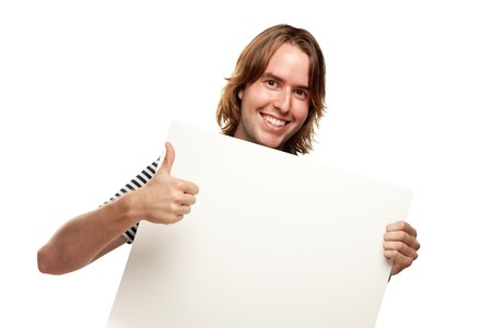 Smiling Young Man with Thumbs Up Holding Blank White Sign Isolated on a White Background. photo