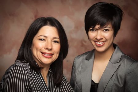 muslin: Attractive Multiethnic Mother and Daughter Studio Portrait on a Muslin Background. Stock Photo