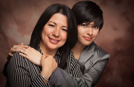 Attractive Multiethnic Mother and Daughter Studio Portrait on a Muslin Background. photo