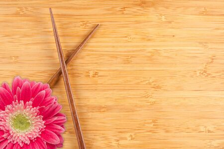 Pink Gerber Daisy and Chopsticks on a Bamboo Background with Copy Space. photo