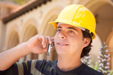 Handsome Hispanic Contractor with Hard Hat Talking on His Cell Phone. photo