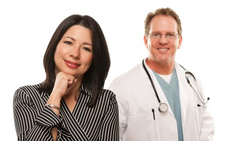 Attractive Hispanic Woman with Male Doctor or Nurse Isolated on a White Background. photo