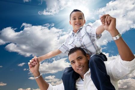 ni�os latinos: Padre de los hispanos y el hijo Having Fun sobre las nubes y el cielo azul con los rayos del sol.